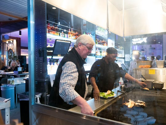 Don Pierce, left, helps Ed Parker at the grill at the