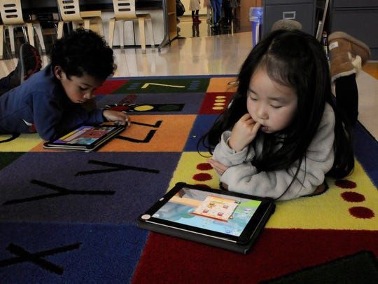 George Washington School kindergarteners Meissa Tham, left, and Yuna Lee work on a program that teaches coding.
