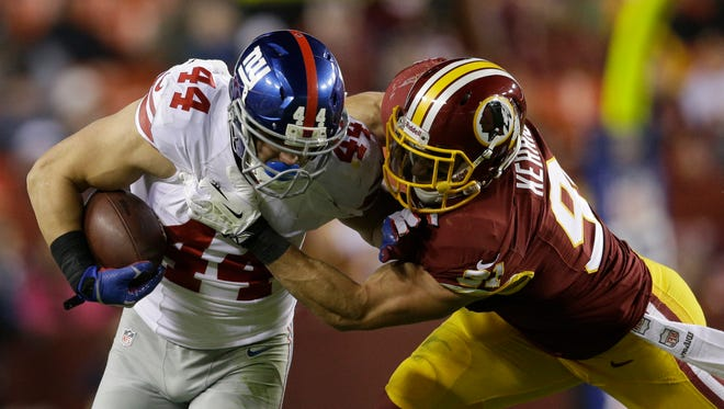 Washington Redskins outside linebacker Ryan Kerrigan (91) brings down Giants RB Peyton Hillis, Dec. 1, 2013, in Landover, Md.