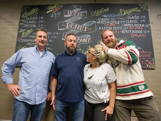 From left, Scott Bussard, Tim Clegg, Kas Clegg and Mark Trusty stand in front of the original menu board at the Hurts Donut corporate office in downtown Springfield on Monday, November 28, 2016.