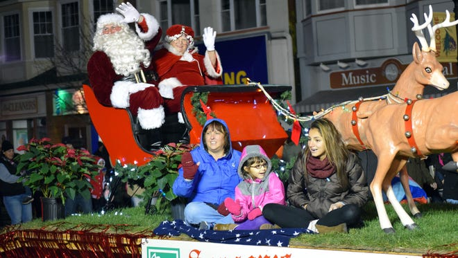 Santa and Mrs. Claus wave to the crowd on Landis Avenue during the Downtown Vineland holiday parade on Saturday, Nov. 26.