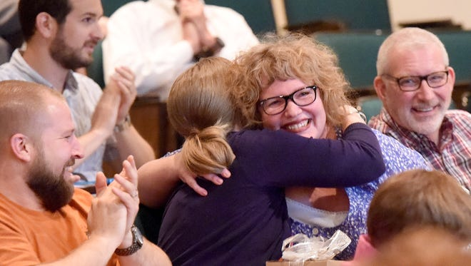 Patty Brower of Three Snugbugs Studios receives a hug from fellow recipient Anna Schoenduby of Latitudes Fair Trade Store after Brower is awarded $10,000 in the Bright ReWired business plan competition. Schoenduby won $12,000. Six aspiring entrepreneurs in the downtown and Newtown districts in Staunton were announced as award recipients Wednesday night, June 17, 2015.