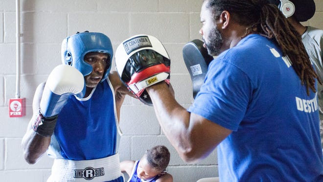Lincoln Center Boxing Club's fighter Stephen Miller warms up with trainer Tyres Williams before his fight Saturday at the Armory.