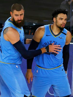 Memphis Grizzlies' Jonas Valanciunas, left, holds back Dillon Brooks during the second half of an NBA basketball game against the Portland Trail Blazers Saturday in Lake Buena Vista, Fla.