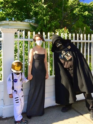 A spaceman, his mother and Darth Vader share a moment during Halloween in June.