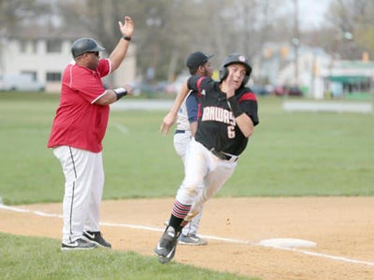 Rahway coach Brad Edwards waves a runner home during