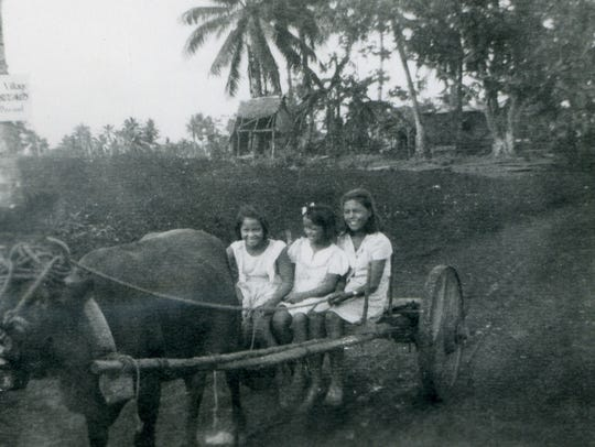 """A photo of Guam youths from Talofofo resident Irene Perez Ploke Sgambelluri-Beruan's collection of postwar images. A sign on the coconut tree at left says, """"Barrigada Village Out of Bounds."""""""