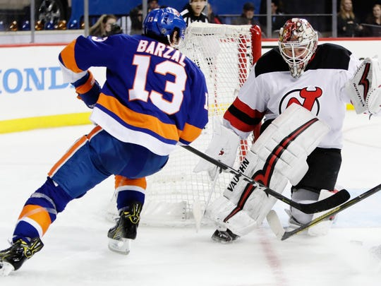 New Jersey Devils goaltender Keith Kinkaid (1) stops a shot on the goal by New York Islanders' Mathew Barzal (13) during the second period of an NHL hockey game Tuesday, Jan. 16, 2018, in New York. (AP Photo/Frank Franklin II)