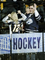 Carrie Underwood points to her Mike Fisher jersey as she performs with Vince Gill, right, during a first-round Stanley Cup playoff series April 20, 2011, in Nashville.