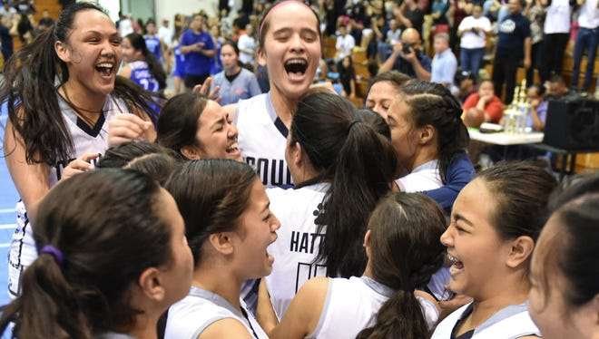 The Academy of Our Lady of Guam Cougars celebrate a victory over the Notre Dame Royals in the IIAAG Girls' Basketball League championship game at the Southern High gym on Dec. 18.