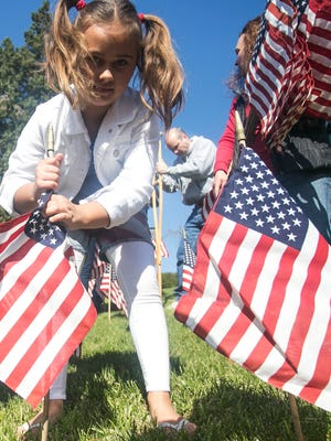 Alexis Martz, 8, of New Salem, places flags in honor of the fallen soldiers at the Prospect Hill Cemetery & Cremation Gardens Flag Re-Creation ceremony Saturday, April 16, 2016. Amanda J. Cain photo