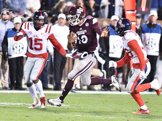 Ole Miss defensive back Myles Hartsfield (15) and defensive back Zedrick Woods (36) attempt to tackle Mississippi State quarterback Keytaon Thompson (10) Thursday in Starkville.