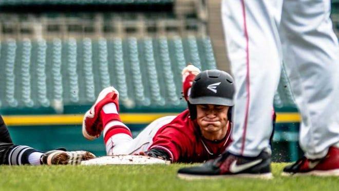 Port Huron High School baseball player Blake Letzgus slides into third base during a game at Comerica Park.
