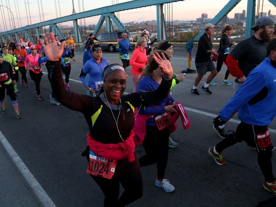 Jacintha Primus, 43 of Windsor, Ontario, Canada waves as she crosses over the Ambassador Bridge on the American side at the third mile mark during the 37th Annual Detroit Free Press/Talmer Bank Marathon in Detroit on Sunday, Oct. 19, 2014. Primus was running the half marathon and finished with a time of 2:41:03.