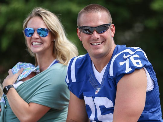 Former Indianapolis Colt Joe Reitz and wife Jill Odom smile to spectators during the Fishers Freedom Festival parade in Fishers, Ind., Sunday, June 25, 2017.