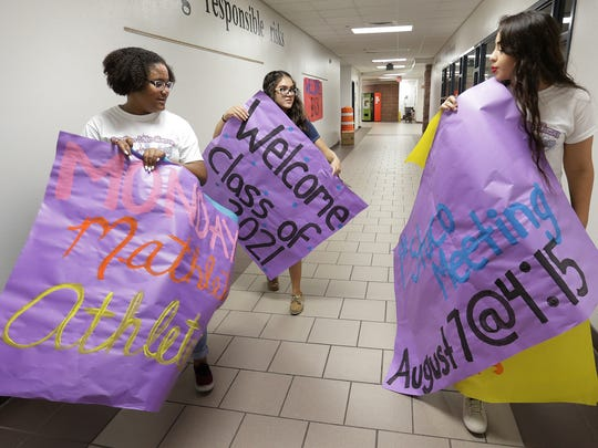 Americas High School student council members Indiya Henry, left, Maranda Miranda, center, and Karla Martinez, right, walk the halls decorating for the first day of school.