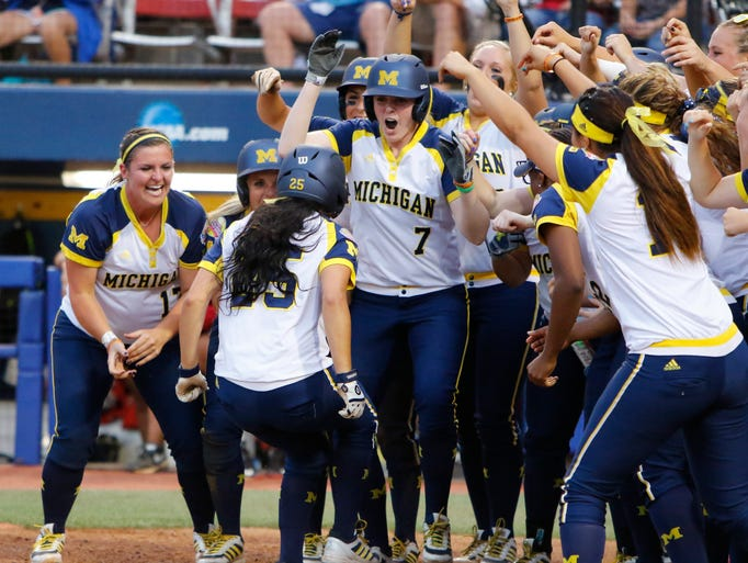 Michigan's Lauren Sweet is greeted at home plate after