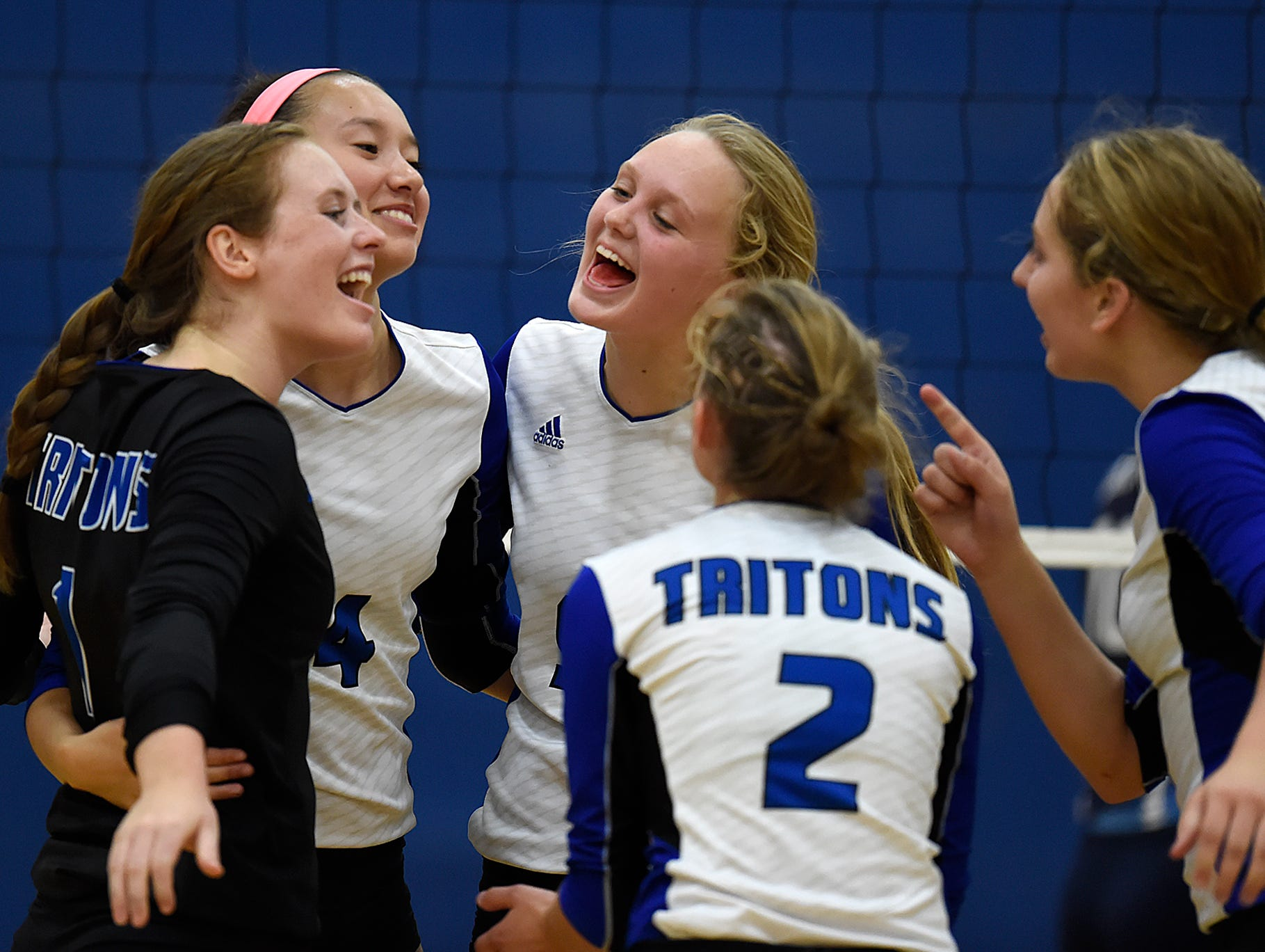 Green Bay Notre Dame senior libero Maureen Schick (left) celebrates with teammates after a point against Bay Port during a Fox River Classic Conference match earlier this season.