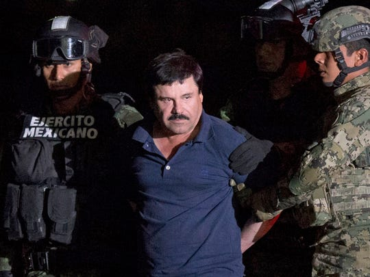 "In this Jan. 8 photo, Mexican drug lord Joaquín ""El Chapo"" Guzmán is escorted by army soldiers  to a waiting helicopter at a federal hangar in Mexico City after he was recaptured after breaking out of a maximum security prison in Mexico"