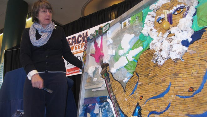 Cindy Zipf, executive director of the Clean Ocean Action environmental group, shows off Tuesday a mosaic of the sea god Poseidon made entirely of trash collected from the sands of the Jersey shore by volunteers.