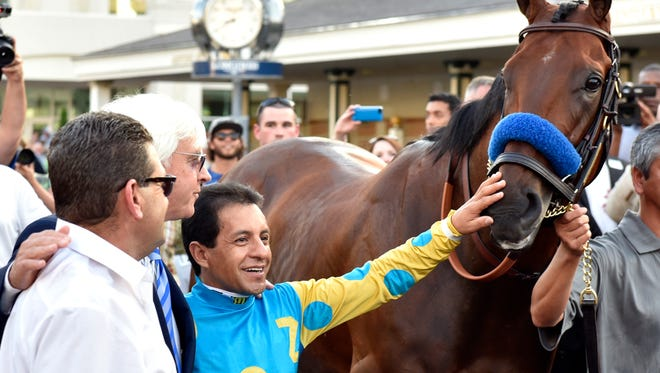 Jockey Victor Espinoza, center, pets the nose of Triple Crown winner American Pharoah during his return to Churchill Downs, Saturday, June 13, 2015. (Timothy D. Easley/Special to the C-J)
