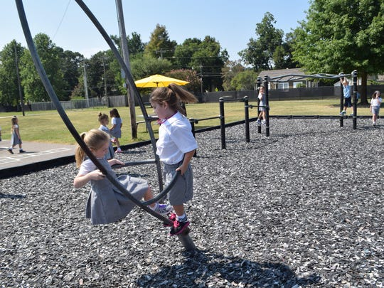First-graders Mary Claire Broadnax (left) and Kyleigh Kramer play at recess on Friday, the first day of school for Our Lady of Prompt Succor School.