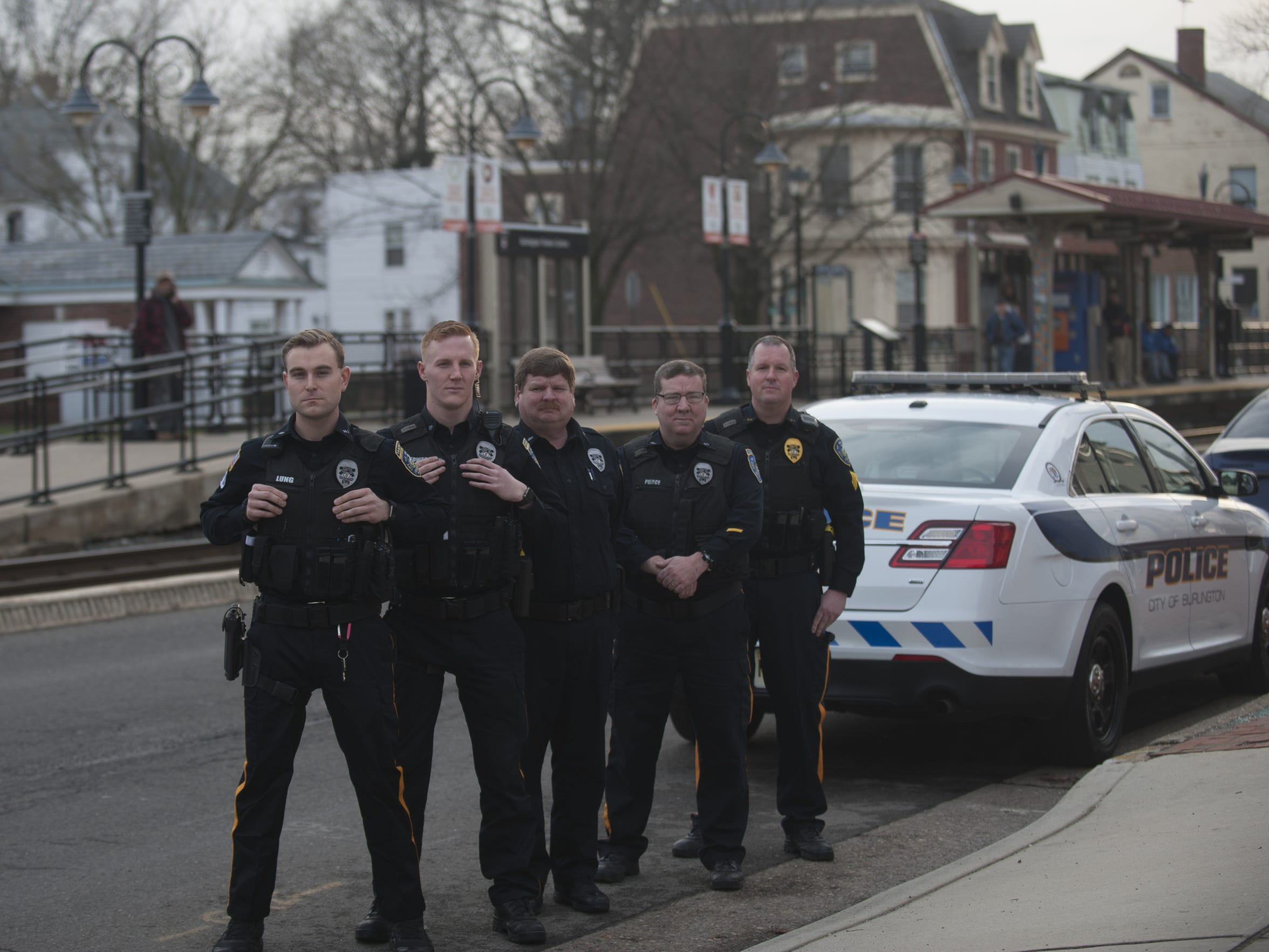 Burlington City police officers (from left) Cameron Lung, David Edwardson, Keith Spencer, Gregory Pierce and Sgt. Ron Fuss stand near the station where they rescued a little girl thrown onto the tracks.