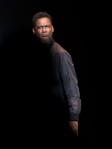 Comedian Chris Rock walks onto the stage to perform