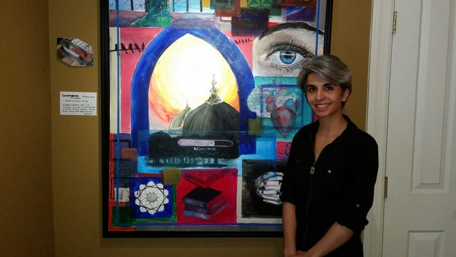 "Arshia Qasim, artist and owner of the Alhamra Art Center in Bernardsville, stands next to one of her paintings, entitled ""Convergence (Loading).""   Her intent, she said, was to show the unity of heart and mind, and how people of different faiths and cultures are enlightened by the same sun."