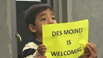 Erick Vasquez, 2, is held by his mother Guadalupe next to his aunt Marcela Vasquez at Des Moines City Council meeting.