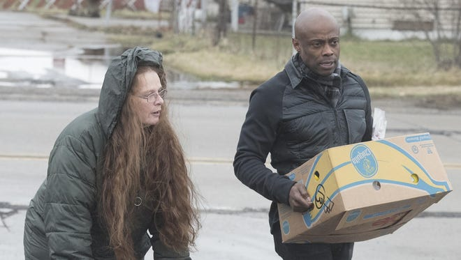 "Motown recording artist KEM helps Virginia Inglot on Tuesday carry water and groceries to her car after stopping at the Salvation Army Flint Beecher Corps Community Center in Flint. The singer is partnering with the Salvation Army and its ""text to give campaign."""