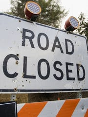 A construction sign alerting of a road closure.