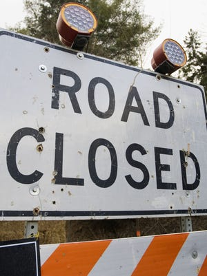 A construction sign alerting of a road closure.