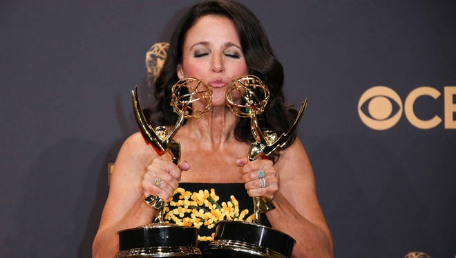 Julia Louis-Dreyfus smooches her awards for outstanding actress and best comedy series in the Emmys trophy room.