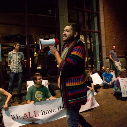 Wes Wisner (center) speaks while he and others protest