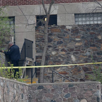 An investigator stands outside the apartment complex
