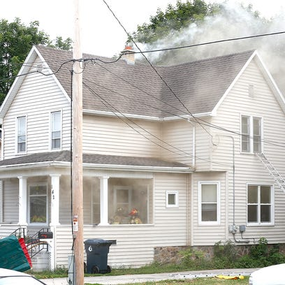 Smoke billows from the chimney area of a house at 142