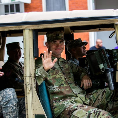 A soldier waves from inside a humvee during the Hanover