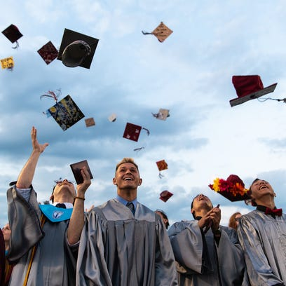 New Oxford High School graduates throw their graduation