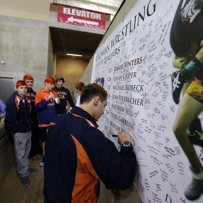 Blackman wrestler Hunter Winters signs a banner remembering