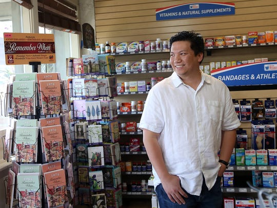 Mark Tan gives a smile as a customer walks in to his Bainbridge Island Community Pharmacy in Winslow on Tuesday, August 8, 2017.