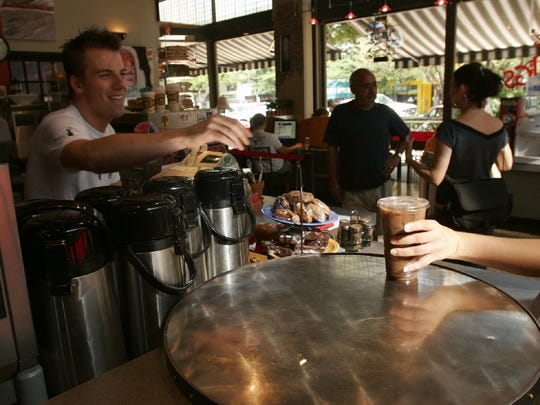 Employee Pete Tolsma serves up an iced coffee drink at Mugs coffee shop in Old Town Fort Collins, July 11, 2005.
