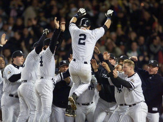 10 /31/2001 - New York, N.Y. - World Series, Game Four --                 Yankees Vs. Diamondbacks --  Derek Jeter jumps into the arms of his teammates after hitting a solo home urn in the tenth inning of the fourth game of the 2001 World Series at Yankee Stadium. ORG XMIT: WS4  JETER   (1D) 68.JPG