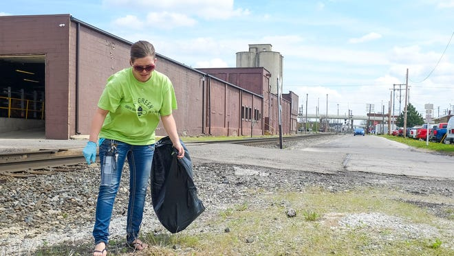 Alyssa Welter picks up litter along the railroad tracks behind the county building as part of the Earth Daycelebrations in Marion on Thursday.