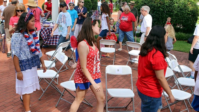 A group participates in a cake walk during the Kell House's Fourth of July Celebration in 2016.
