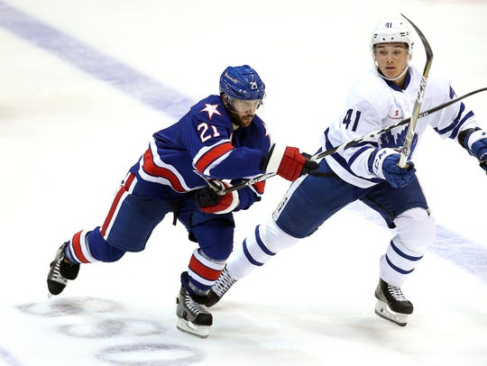 Rochester's Brian Gionta (21) tries to slip by Toronto's