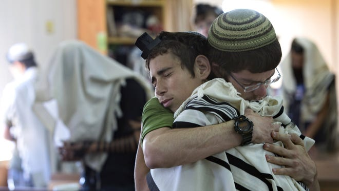 Israeli Jewish religious students hug prior to a prayer at the synagogue where two of the missing Israeli teens studied, in the Jewish settlement of Kfar Etzion, Sunday, June 15, 2014. Israeli security forces searched the West Bank for a third day Sunday, looking for three missing teenagers, including an American, who they fear have been abducted by Palestinian militants. (AP Photo/Sebastian Scheiner)