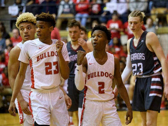 Bosse's Mekhi Lairy (2) talks to a referee as his teammates Bosse's Javen Layne (10) and Jaylen Minor (23) stand beside him during the IHSAA Class 3A semistates against the Danville Warriors at the Hatchet House in Washington, Ind., Saturday, March 17, 2018. The Bulldogs will advance to next Saturday's state championship after defeating the Warriors 64-61.