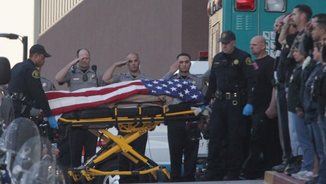 Law enforcement officers salute as the body of a Bay Area Rapid Transit police officer draped with the American flag is loaded into an Alameda County Sheriff's Coroner vehicle, Tuesday.
