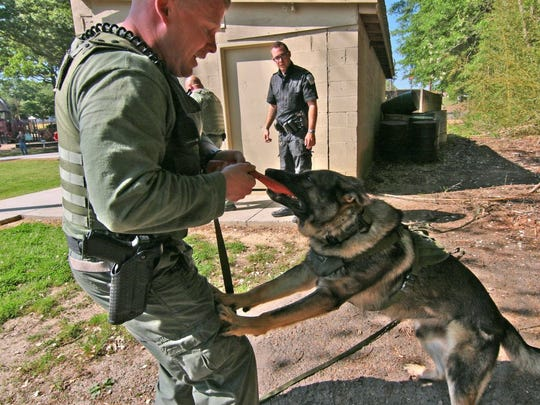 Shawn Davis (right) watches Eric Scott reward Sandro, a German Shepard during Anderson County Sheriff's Office K9 Unit training in Mineral Spring Park in Williamston. Davis, a resource officer in Anderson School District Five working for the county sheriff's office, is scheduled to join the K9 unit and get the next dog from Pennsylvania.